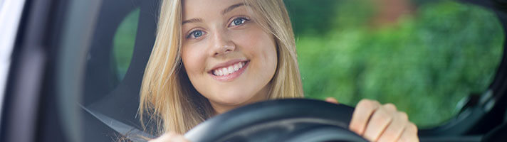 A young woman smiles behind the wheel